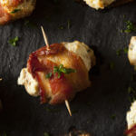 Need a keto appetizer recipe? You can't go wrong with these bacon wrapped keto stuffed mushrooms! Easy low carb, high protein mushrooms filled with cream cheese, cheddar, and Parmesan & wrapped in bacon make fabulous finger foods for a crowd! Try this delicious keto stuffed mushroom appetizer at your next party! Nobody will guess it's healthy keto diet food!